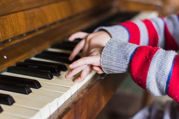 primer-plano-mano-ninos-tocando-teclas-piano_23-2147873702